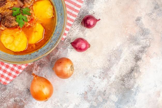 Draufsicht bozbash suppe küchentuch gelbe und rote zwiebeln auf nacktem hintergrund
