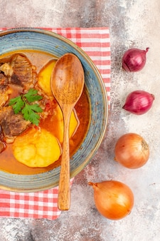 Draufsicht bozbash-suppe mit holzlöffel auf nacktem hintergrund