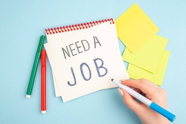 Draufsicht braucht einen job, der auf einer haftnotiz in weiblichen händen mit roten und grünen markierungen auf blauem stift geschrieben wird