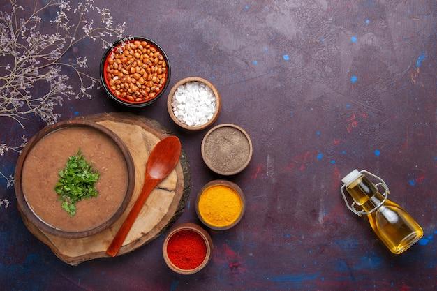 Draufsicht braune bohnensuppe köstliche gekochte suppe mit gemüse und gewürzen auf dunkler oberfläche abendessensuppe mahlzeit bohnenfutter