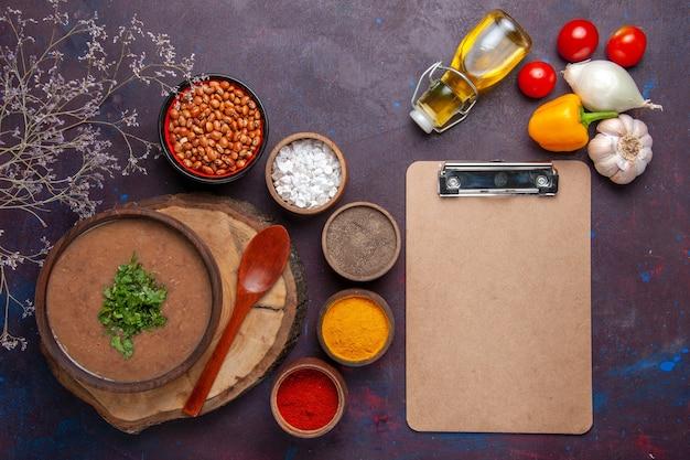 Draufsicht braune bohnensuppe köstliche gekochte suppe mit verschiedenen gewürzen auf der dunklen oberfläche abendessensuppe mahlzeit bohnenfutter