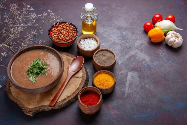 Draufsicht braune bohnensuppe köstliche gekochte suppe mit verschiedenen gewürzen auf dunklem boden abendessen suppe bohnen essen mahlzeit