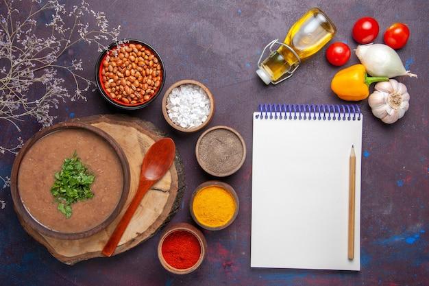 Draufsicht braune bohnensuppe köstliche gekochte suppe mit verschiedenen gewürzen auf dunklem schreibtisch abendessen suppe mahlzeit bohnenfutter