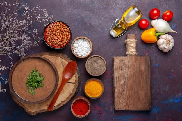 Draufsicht braune bohnensuppe köstliche gekochte suppe mit verschiedenen gewürzen auf dunkler oberfläche abendessensuppe bohnennahrung mahlzeit
