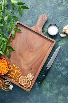 Draufsicht brauner hölzerner schreibtisch mit orangefarbenen linsen auf der dunkelblauen oberfläche der alten küche färbt fleischfleischmetzger-küchenmesserfutter