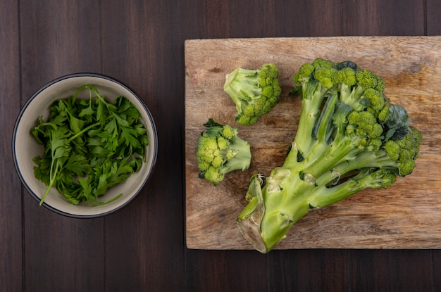 Draufsicht brokkoli auf schneidebrett mit petersilie in schüssel auf hölzernem hintergrund