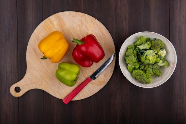 Draufsicht brokkoli in der schüssel mit paprika auf schneidebrett mit messer auf holzhintergrund