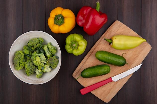 Draufsicht brokkoli in der schüssel mit paprika-gurken auf schneidebrett mit messer auf hölzernem hintergrund