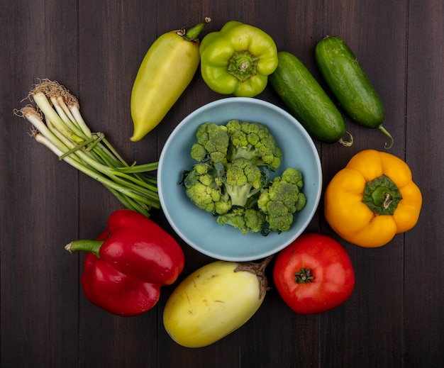 Draufsicht-brokkoli in der schüssel mit paprika-gurken-schnittlauch und tomate auf hölzernem hintergrund
