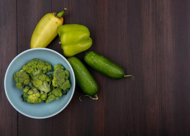 Draufsicht brokkoli in der schüssel mit paprika und gurken auf hölzernem hintergrund