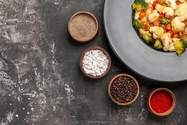 Draufsicht brokkoli und blumenkohlsalat in schwarzer schüssel verschiedene gewürze in schalen auf dunkler oberfläche
