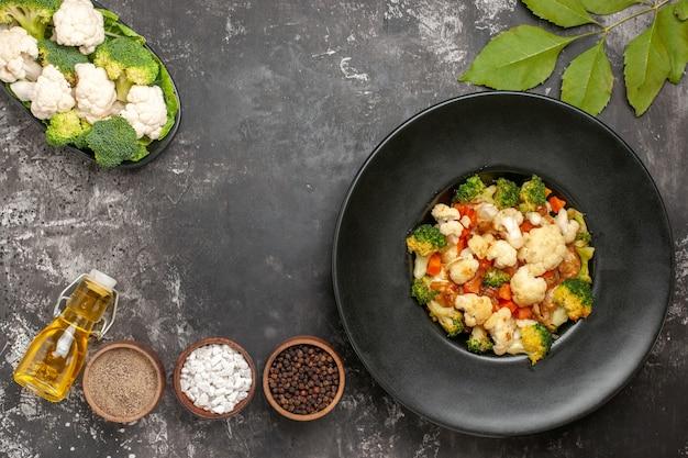Draufsicht brokkoli und blumenkohlsalat in schwarzer schüssel verschiedene gewürze in schalen öl rohes gemüse auf teller auf dunkler oberfläche