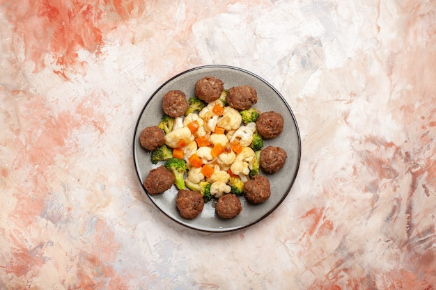 Draufsicht brokkoli und blumenkohlsalat und fleischbällchen auf teller auf nacktem, isoliertem, freiem raum