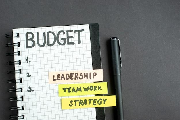 Draufsicht budgetnotiz im notizblock mit stift auf dunkler oberfläche strategie geschäftsmarketing teamarbeit büroführung job erfolg