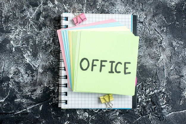 Draufsicht büro geschriebene notiz mit bunten aufklebern und heft auf grauem hintergrund