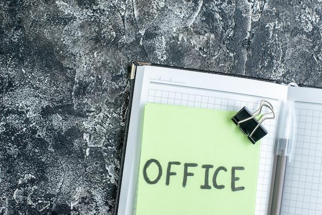 Draufsicht büro geschriebene notiz mit heft und stift auf grauem hintergrund