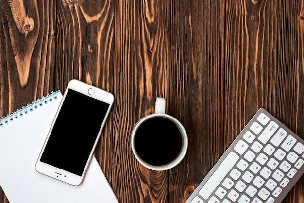 Draufsicht büro holzschreibtisch mit einer tasse kaffee und smartphone - copyspace