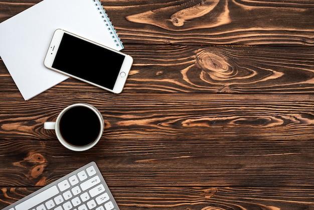 Draufsicht büro holzschreibtisch mit einer tasse kaffee und smartphone