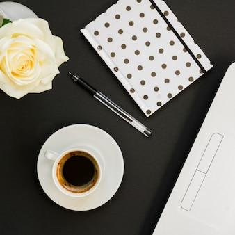 Draufsicht bürotisch schreibtisch. arbeitsplatz mit laptop, tupfentagebuch und kaffeetasse auf schwarzem