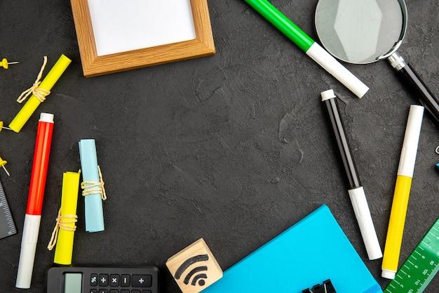 Draufsicht bunte bleistifte mit bilderrahmen und taschenrechner auf dunklem hintergrund schulzeichnung farbfoto