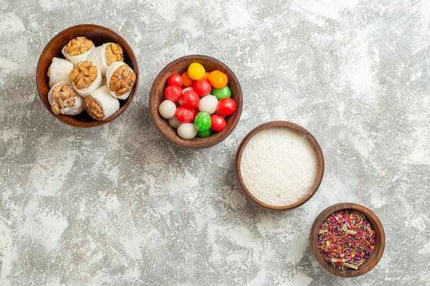 Draufsicht bunte bonbons mit nusskonfekt auf weißem tischfarbenbonbonregenbogen