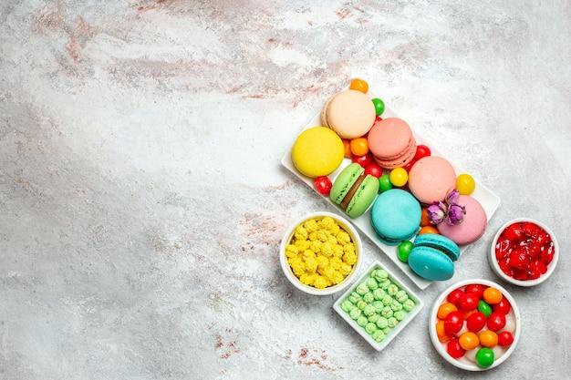 Draufsicht bunte köstliche macarons kleine kuchen mit bonbons auf hellem weißraum