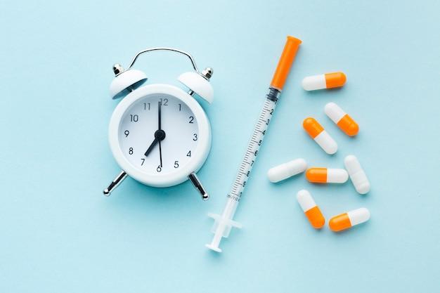Draufsicht bunte pillen und weiße uhr mit spritze