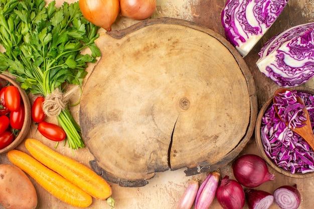 Draufsicht bunte salatzutaten aus einem rotkohlbündel petersilie-roma-tomaten karottenkartoffeln und zwiebeln um ein schneidebrett auf einem hölzernen hintergrund mit platz für text