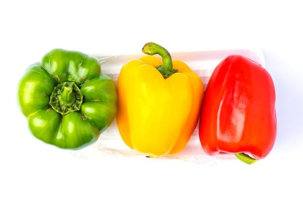 Draufsicht buntes gemüse, gelb, grün und rot, paprika auf schaumstoffschale lokalisiert auf weißem hintergrund
