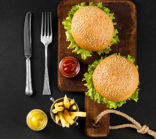 Draufsicht burger und pommes auf schneidebrett