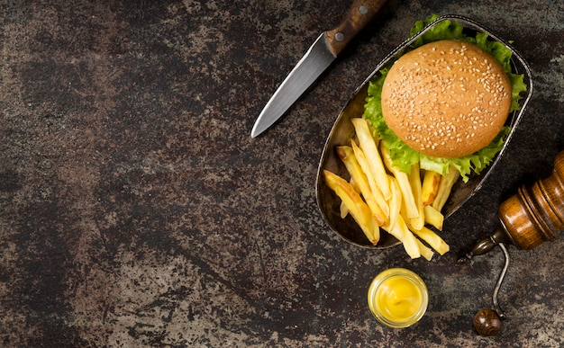 Draufsicht burger und pommes mit messer und kopierraum