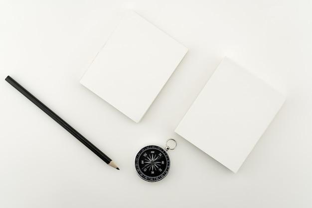Draufsicht business-objekte von weißbuch, bleistift und kompass auf papierarbeit isoliert auf weißem hintergrund flache laienzusammensetzung.