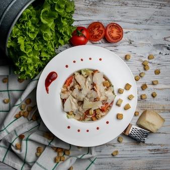 Draufsicht caesar salat mit crackern und käse und salat in weißer platte