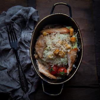 Draufsicht caesar salat mit lappen und tomate und gabel in platte