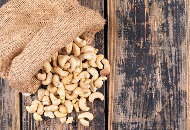 Draufsicht cashewnüsse im sack auf holztisch