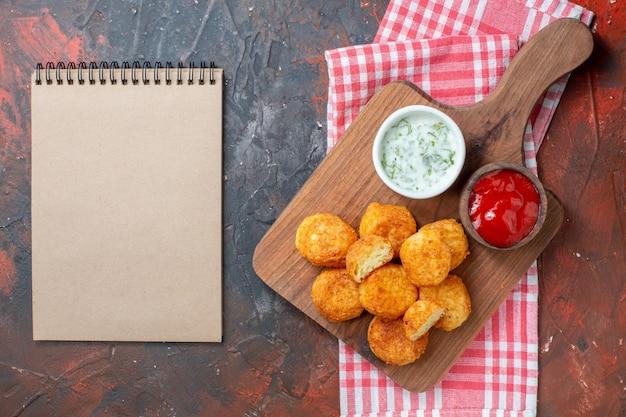 Draufsicht chicken nuggets auf holzbrett mit saucen rot weiß kariertes küchentuch notebook auf dunklem tisch