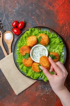 Draufsicht chicken nuggets salat auf teller salz und schwarzer pfeffer in holzlöffel kirschtomaten auf dunklem tisch