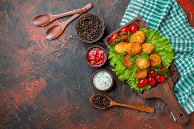 Draufsicht chicken nuggets salat kirschtomaten auf holzbrett schwarzer pfeffer in schüsselsaucen in kleinen holzschalen holzlöffel auf dunklem tisch frei
