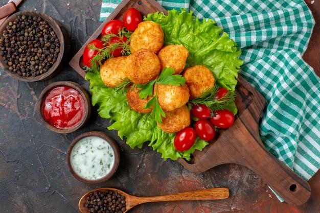 Draufsicht chicken nuggets salat kirschtomaten auf holzbrett schwarzer pfeffer in schüsselsaucen in kleinen holzschalen holzlöffel auf dunkler oberfläche
