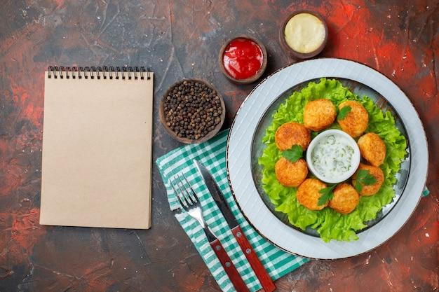 Draufsicht chicken nuggets salat und sauce auf tellersaucen und schwarzer pfeffer in kleinen schüsseln, gabel und messernotizbuch auf dunklem tisch