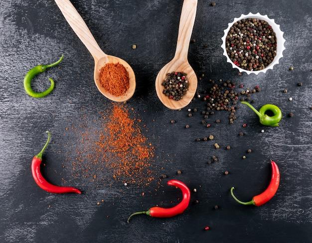 Draufsicht chili pfeffer mit gewürzen in holzlöffeln auf schwarzem stein horizontal
