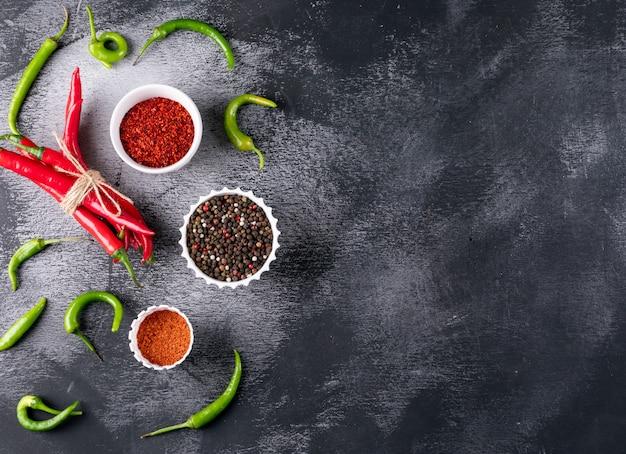 Draufsicht chili pfeffer mit gewürzen in weißen schalen auf schwarzem stein horizontal