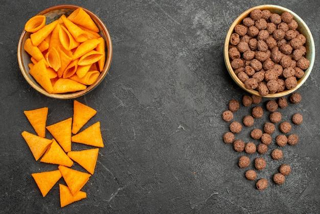 Draufsicht-cips und -flocken auf dunklem hintergrund-snackmahlzeit-milchfrühstück Kostenlose Fotos