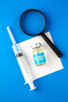 Draufsicht covid-impfstoff mit lupe und injektion auf die pandemie-virus-medikamente des krankenhauses mit blauer oberfläche