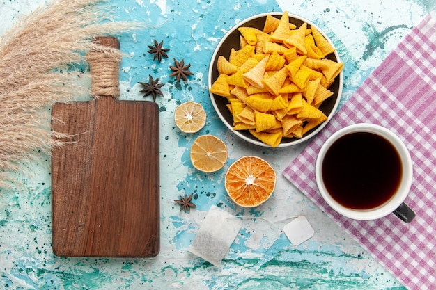 Draufsicht-crackerchips mit tasse tee auf der blauen oberfläche