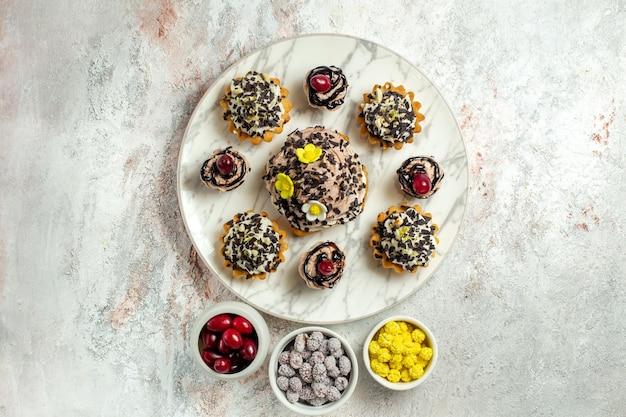 Draufsicht cremig leckere kuchen mit bonbons auf hellweißer oberfläche teekuchen keks süße geburtstagscreme