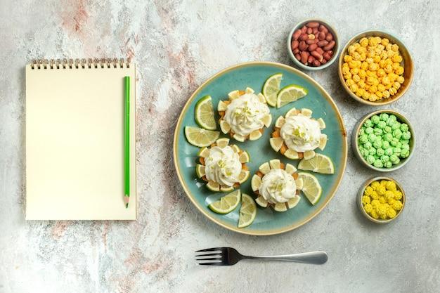 Draufsicht cremig leckere kuchen mit zitronenscheiben und bonbons auf weißer oberfläche kuchen keks keks sahnetee süß