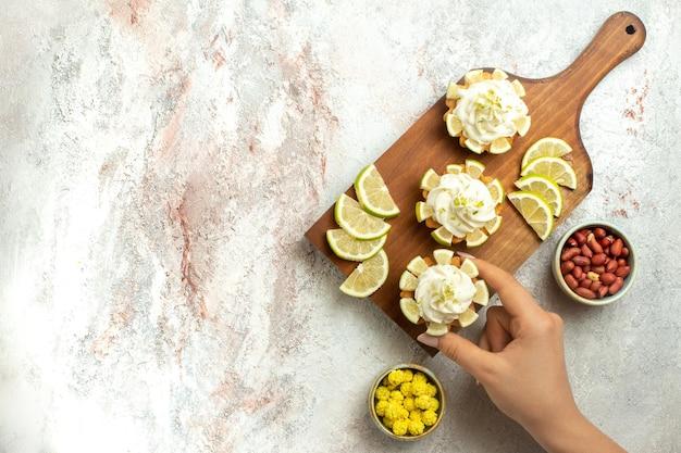 Draufsicht cremige köstliche kuchen mit zitronenscheiben und bonbons auf weißem oberflächenkuchenkeksplätzchen süßer sahnetee