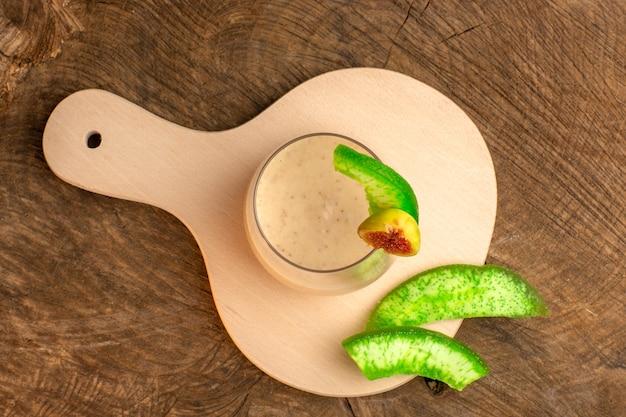 Draufsicht cremiger cocktail in kleinem glas mit blumen auf dem braunen schreibtischcocktailcreme-farbfoto-dessert
