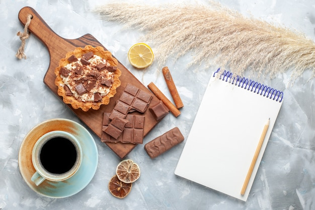 Draufsicht cremiger kleiner kuchen mit schokoriegeln tee-notizblock und zimt auf leichtem schreibtisch süßer kuchen zuckercreme-schokolade